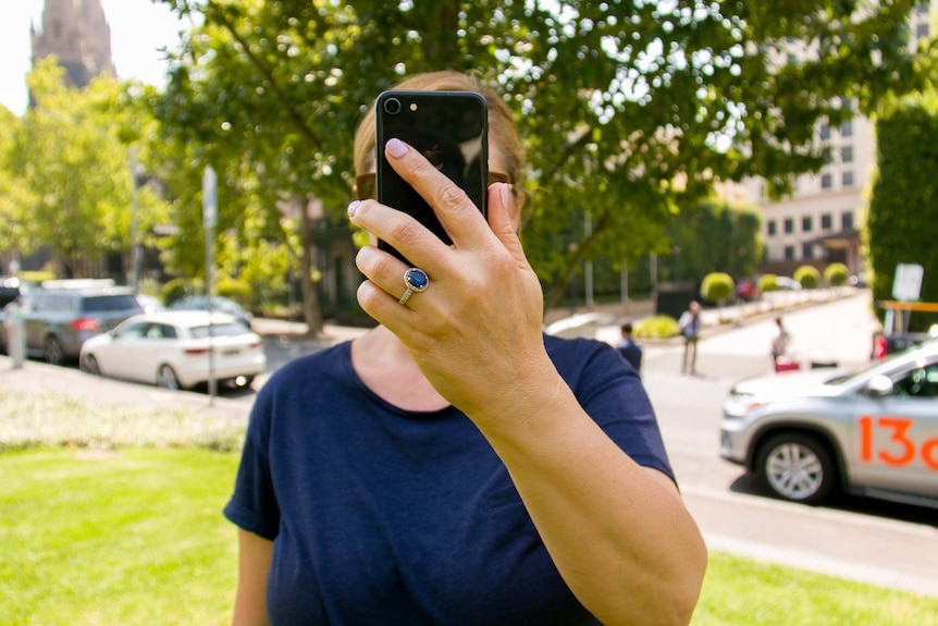 A woman hold a smart phone in front of her face.
