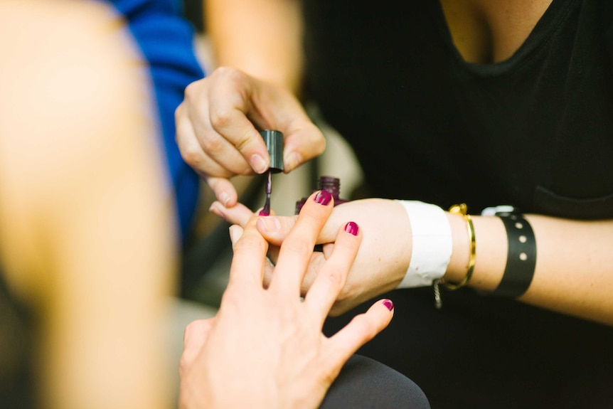 A person puts nail polish on another person's finger nails.