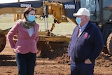 Queensland Premier Annastacia Palaszczuk and businessman John Wagner chat in front of earthmoving equipment.