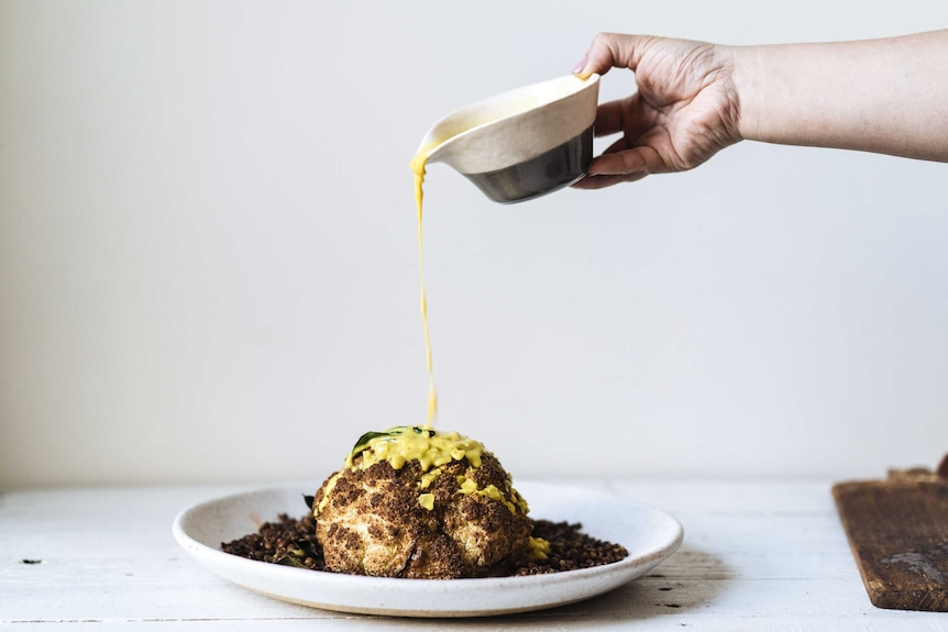 Turmeric coconut sauce is poured over a roasted coconut and fried lentils from a height, a dramatic dish for special occasions.