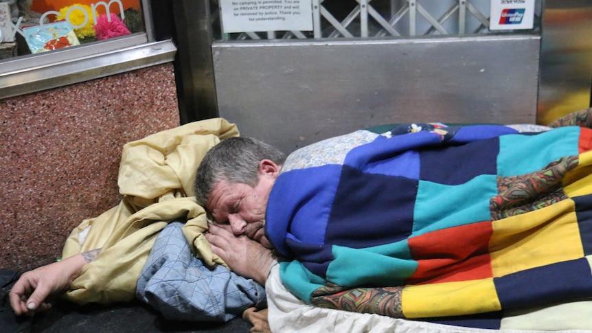 A homeless person sleeping rough.