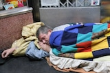 A homeless person sleeping rough.