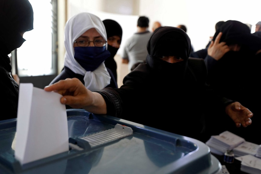 A woman in a niqab puts an envelope in a plastic box.