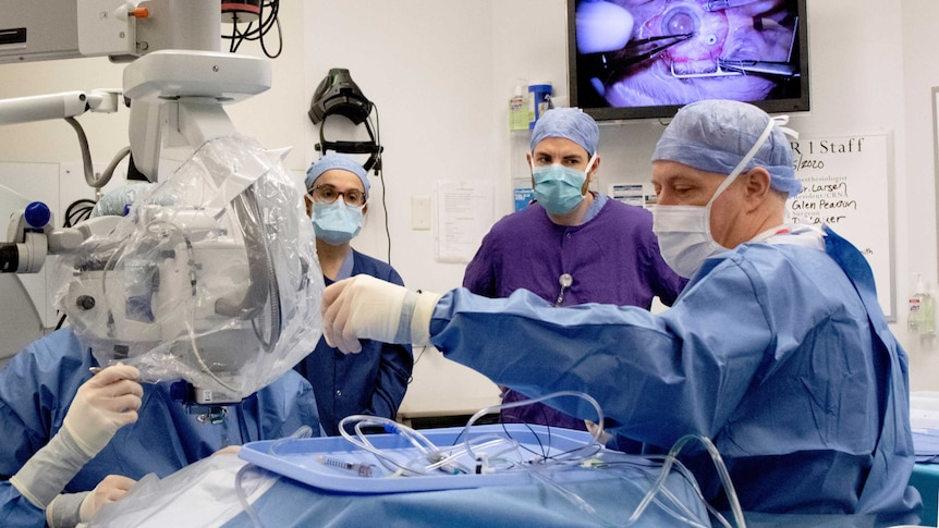 A doctor in blue hospital scrubs and face mask reaches for surgical equipment watched by colleagues.
