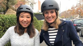Two women wearing bike helmets on a suburban street.