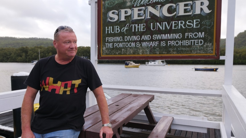 Man leans on wooden table, sign behind him reads Spencer hub of the universe