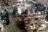 A bird's eye view of a large shed with men at different woodworking stations.