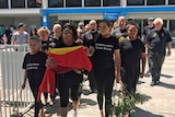 Aboriginals file out of  Launceston airport with remains in box under flag.