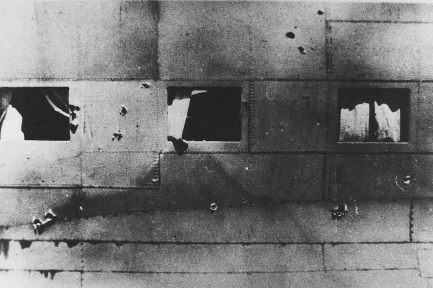 Black and white photo of the side of a plane showing bullet holes in the metal of the fuselage and three windows.