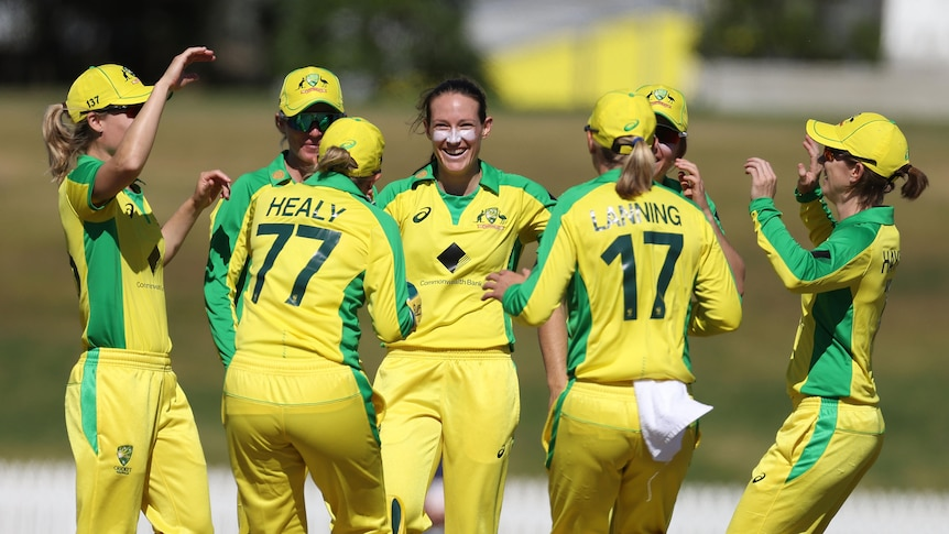 Megan Schutt smiles and is hugged by other women wearing yellow and green cricket kit