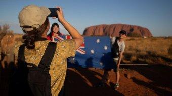 A woman takes a photo near Uluru.