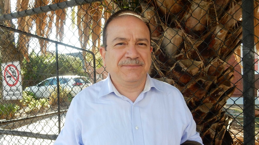 Tamer Antakly stands in front of a wire fence with a palm tree behind him