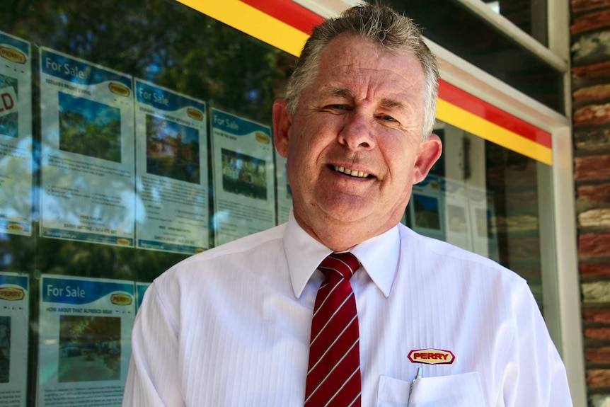 a head and shoulders shot of a man in a white shirt and red tie standing outside a real estate agency.