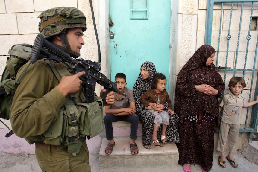 Israeli soldier walks past Palestinians