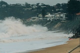 Waves break near homes causing cliffs to form from erosion