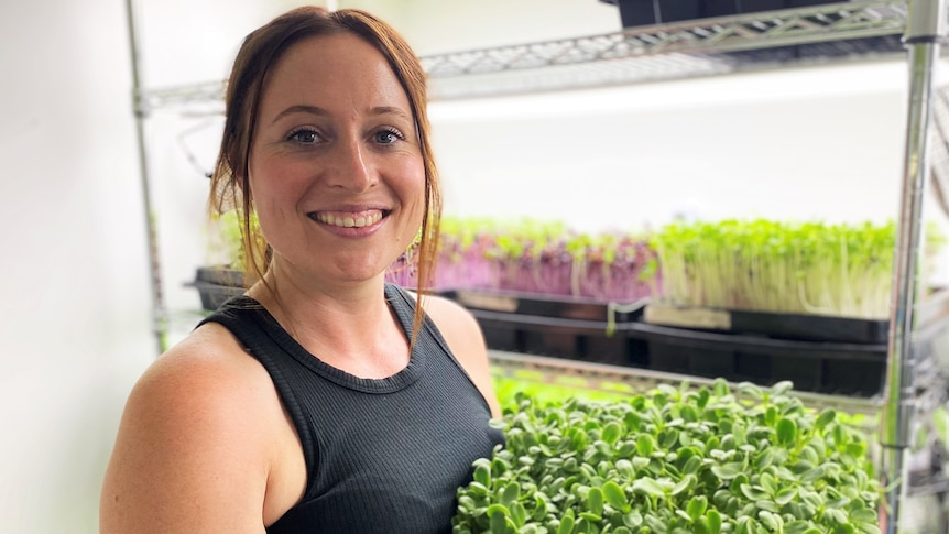 Woman holds tray on microgreens