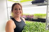 Woman holds tray on microgreens