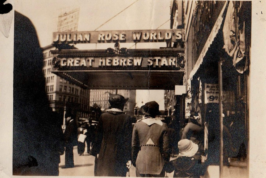 """People walk past a theatre. It's sign reads """"Julian Rose World's Great Hebrew Star"""". Written on the picture is 'Frisco 1914'."""