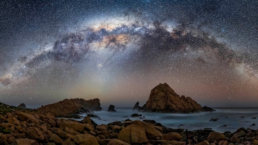 The night sky, over an ocean with rocks and twinkling stars