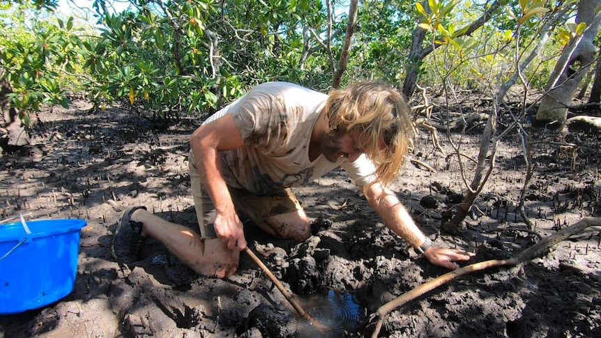 A man crouched down in the mud digging in a hole.
