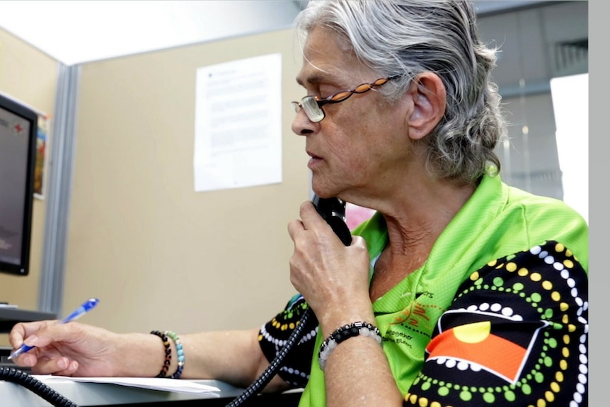 An older woman wearing a shirt decorated with Indigenous art speaks on the phone.