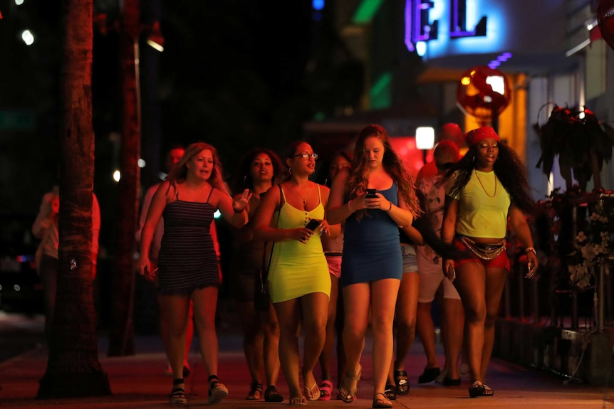 A group of young women walking down a street at night
