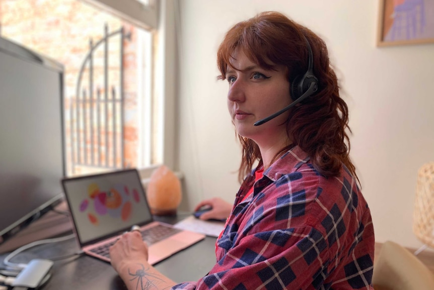 A woman with red hair, wearing a red and blue flannel shirt, sits at a computer wearing a headset.