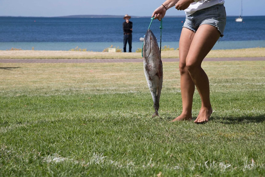A woman's legs seen from the waist down holds a tuna on a rope that is almost the same length as her legs, by the seaside.