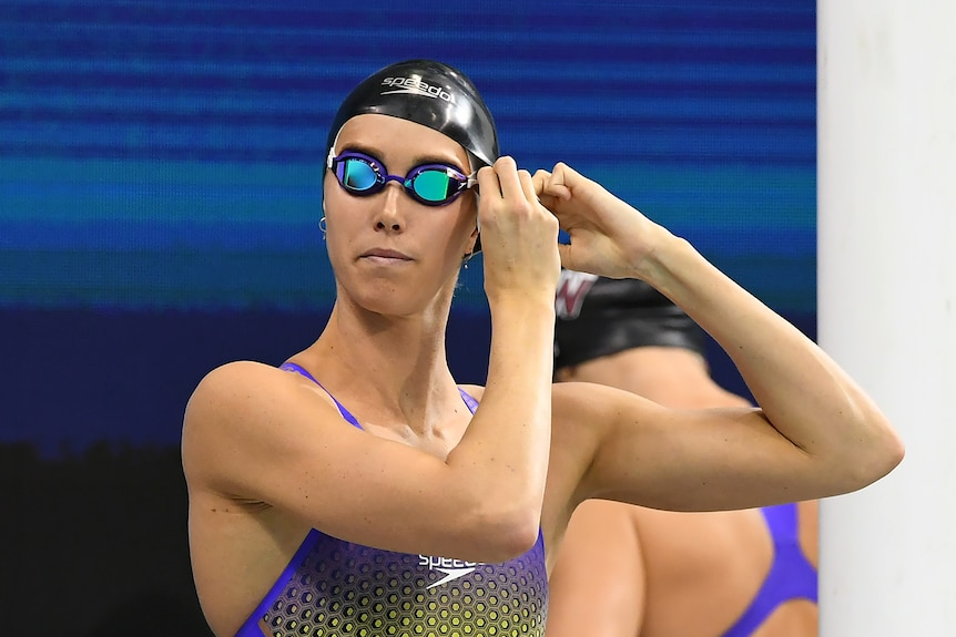 Female swimmer with black cap and goggles, adjusts goggle strap