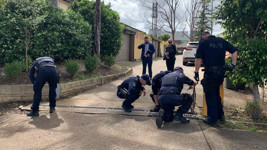 Police officers search outside a home