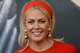 Samantha Armytage looks slightly to the left as she smiles. She wears a red dress, matching headband and gold earrings.
