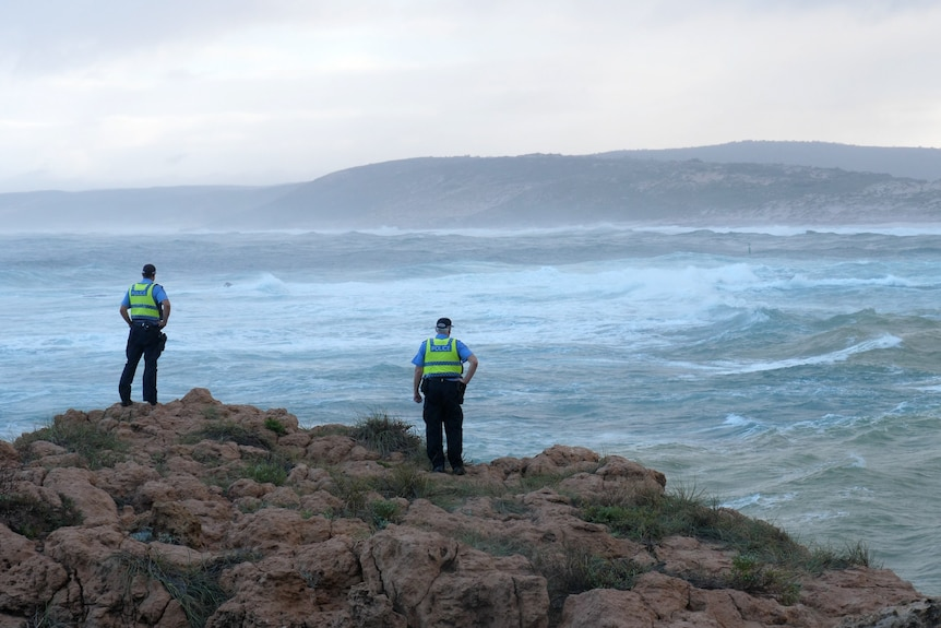 Two police officers wearing hi-vis shirts stand looking out to a misty sea