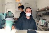 Woman in black jacket wearing face mask, holding out a green takeaway coffee cup