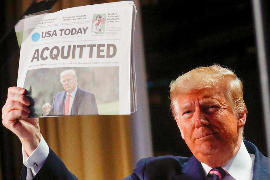 """Donald Trump holding a newspaper up with the headline """"Acquitted"""""""