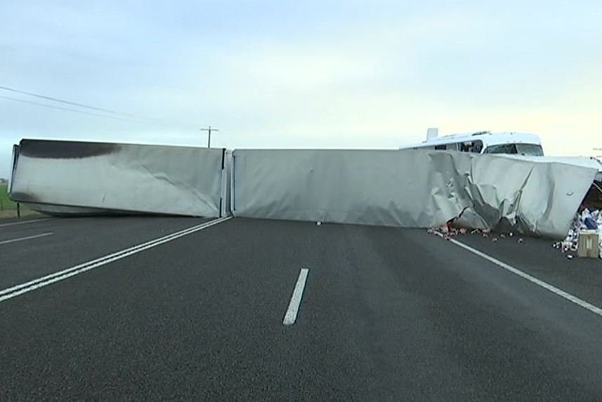 White truck trailers lie across both lanes of the Western Highway, entirely blocking the road.