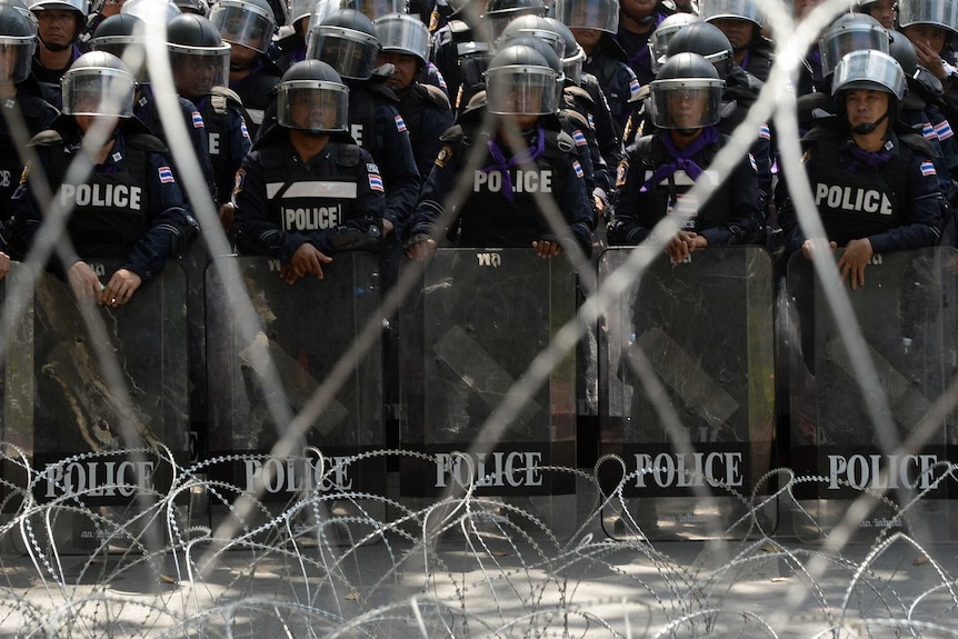 Policemen form a line behind barbed wires inside police headquarters during an anti-government protest in Bangkok