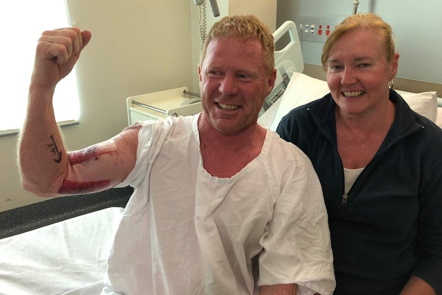 man and woman smiling as man flexes biceps with bloody bite marks