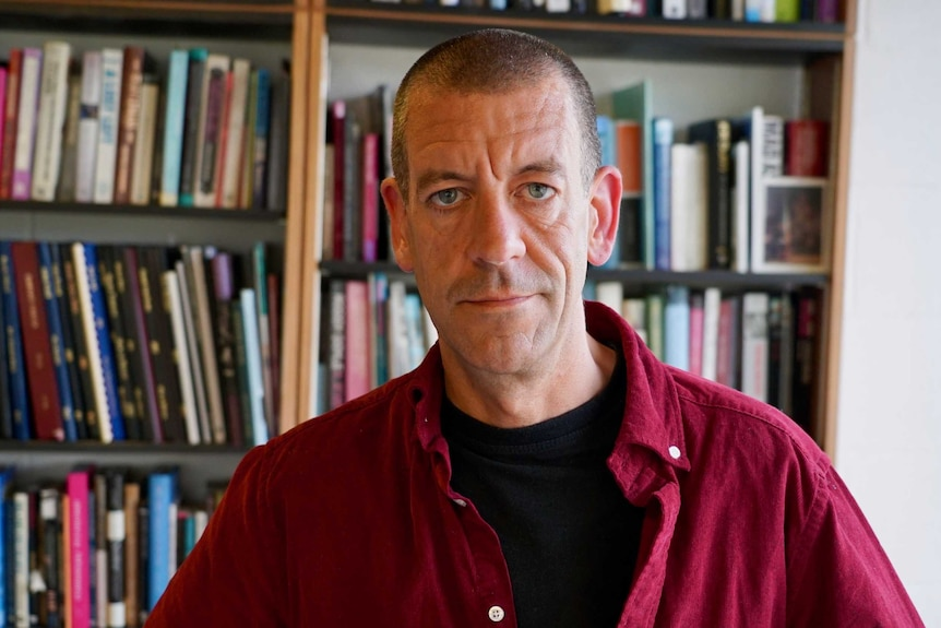 Diarmaid Ferriter stands in front of a bookshelf