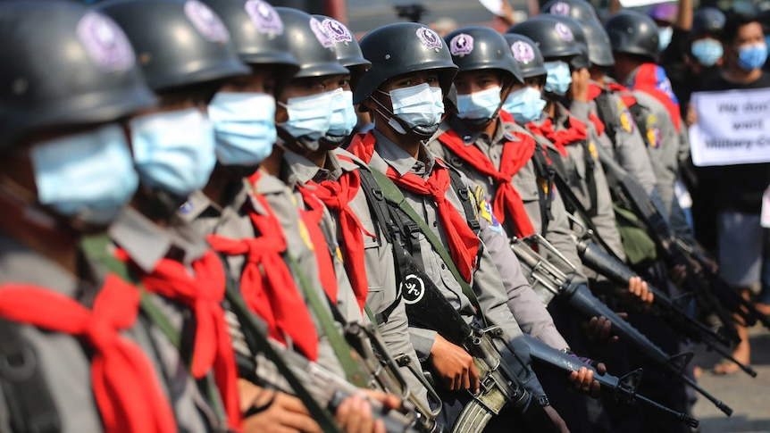 Armed riot police are seen near protesters in Naypyitaw, Myanmar.