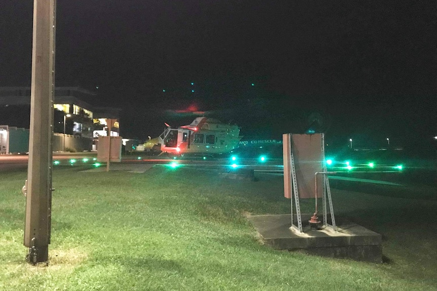 Helicopter lands at Mackay hospital at night.