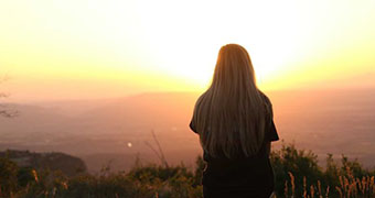 Woman looking at the sunset.