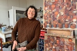 Artist Lucy Culliton smiles at the camera with artwork next to her, wearing a brown jumper