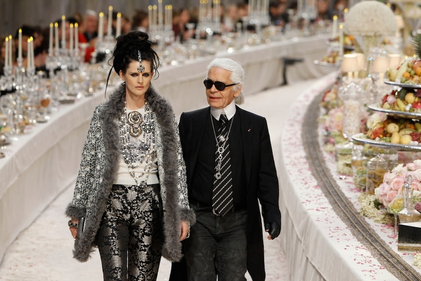 Stella Tennant standing next to Karl Lagerfield walking past tables with candles and food on them