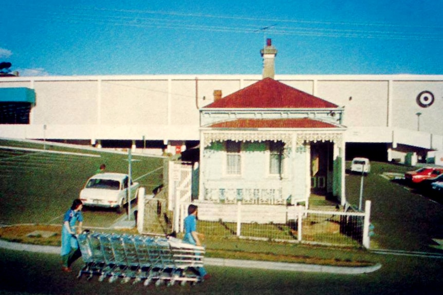 A colour photograph of Mary Ann Campigli's home, surrounded by a carpark on three fronts. A person wheels a trolley out the fr