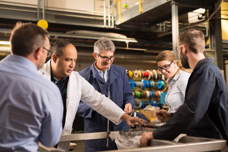 CSIRO team members stand around the H membrame technology.