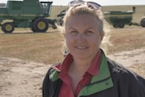 Blonde woman smiles in front of harvest machinery
