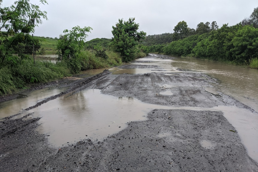 Water flows over a road from ponds at the New Chum dump site.
