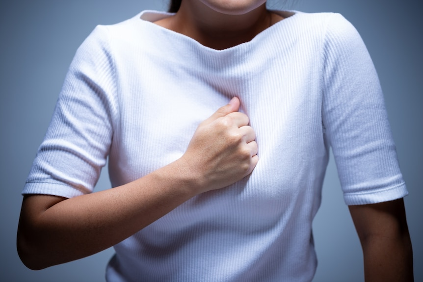 Closeup of the torso of a woman who is pressing her fist into her breastbone.