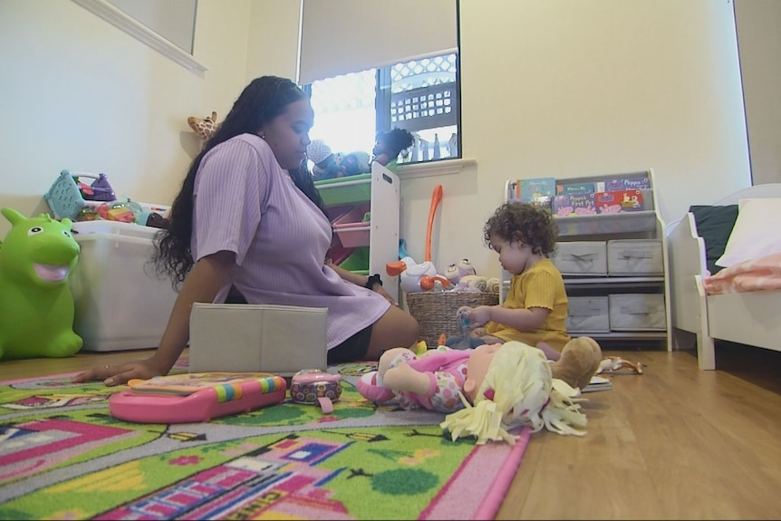 Ms McIntosh and her daughter playing on the floor of her room, surrounded by toys