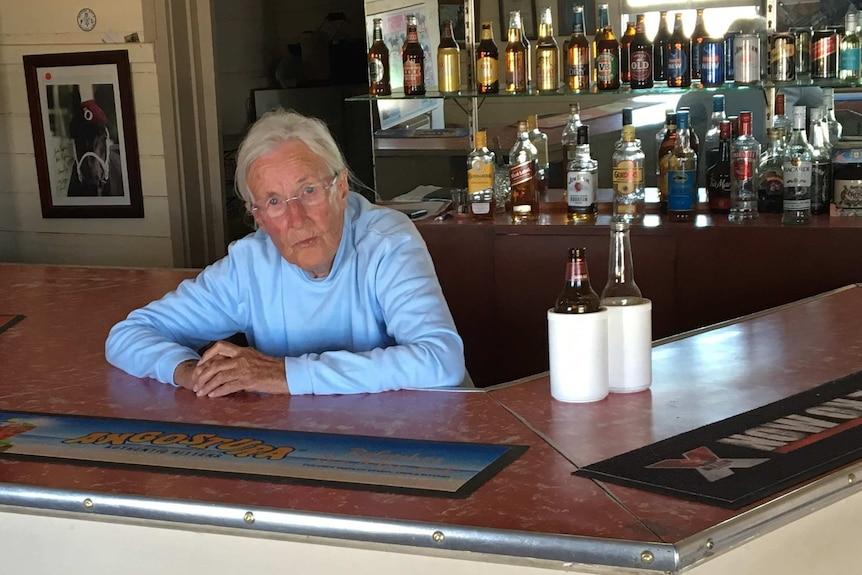 An elderly woman behind the bar in a pub